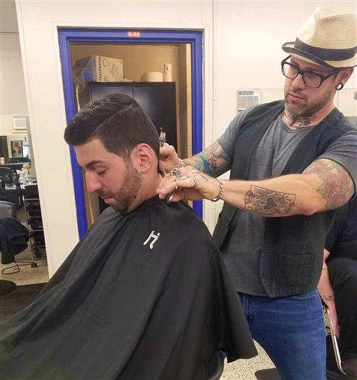 Customer receives a haircut from stylist.