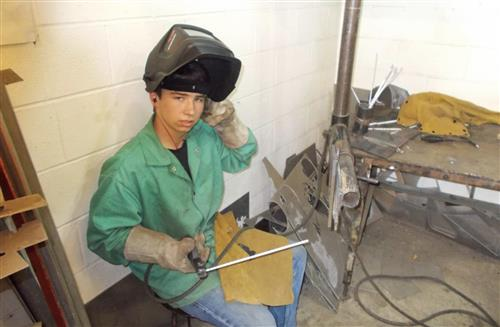 Student takes a break from welding to take a picture.